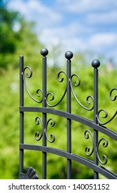 Black-painted iron fence, garden in the background