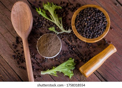 A lot of blackpeppers on wooden background