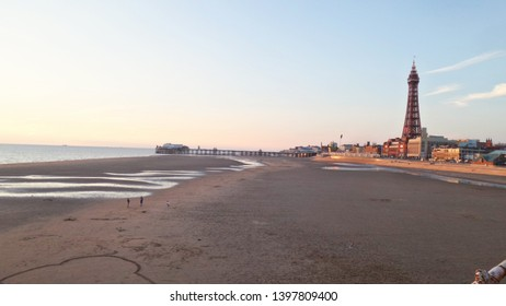 Blackpool beach at dusk with a view of Blackpool tower and the Irish Sea on a Summer's Evening in England's North Western Coast