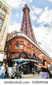 Blackpool, England - August 15th 2016 : Young female street performer entertains the public  with soap bubbles outside the world famous Blackpool tower.