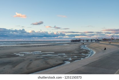 BLACKPOOL, ENGLAND - OCTOBER 26, 2018: Tourists stroll on Blackpool Beach at sunset during an autumn weekend in late October 2018. Blackpool is one of Englands favorite seaside resorts.