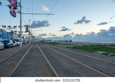 BLACKPOOL, ENGLAND - OCTOBER 26, 2018: Tram tracks between Blackpool Beach and the Promenade at sunset during an autumn weekend. Blackpool is one of Englands favorite seaside resorts.