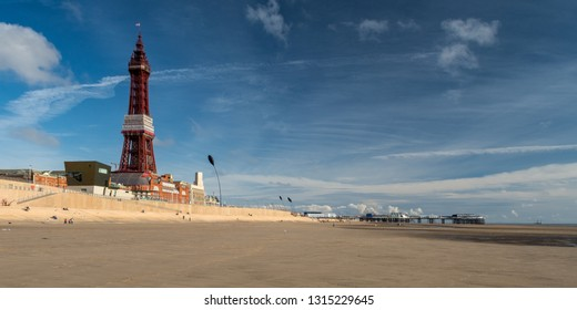 Blackpool, England, UK - August 1, 2015: Tourists walk along the sands of Blackpool Beach under the iconic Blackpool Tower and Blackpool North Pier on a summer day.