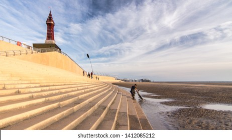 Blackpool, England, UK - August 1, 2015: People walk along the steps of Blackpool Promenade sea wall, with the iconic Blackpool Tower and Blackpool Middle Pier behind.