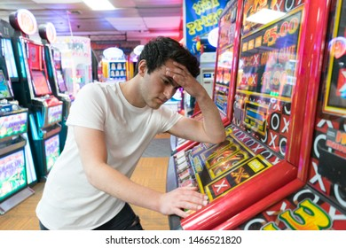 Blackpool, Lancashire. 7th July 2019: Young man in casino gambling on slot machines suffering from migrane from gambling
