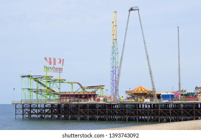 Blackpool, Lancashire/UK - May 7th 2019: South Pier at Blackpool with roller coaster and bungee ride on blue sky with blue sea and sand