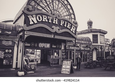 BLACKPOOL, UK - NOVEMBER 3, 2015: Entrance to North Pier, Blackpool.  A man is stood outside on his phone.