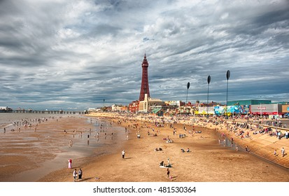 Blackpool, United Kingdom - August 06, 2016: Blackpool's famous Golden Mile beach. People sunbathing in the beach. Blackpool Tower in the background. HDR.