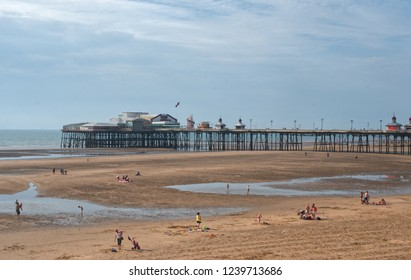 Blackpool, United Kingdom - July 15,2013. Beautiful view of Blackpool pier and People relaxing and having fun on Pleasure Beach in Blackpool, United Kingdom.