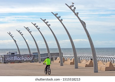 Blackpool,Lancashire/England - 23.09.2019 - Cyclist riding his bike past modern lamp post with visit Blackpool banner in the background