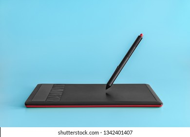 Black-red graphics tablet and levitating stylus on a light blue solid background.