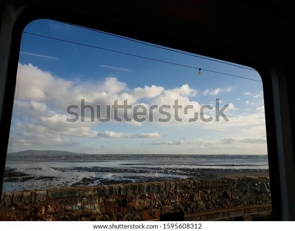 BLACKROCK, CO. DUBLIN, IRELAND - DECEMBER 8, 2019: Seascape seen through the window of a moving train. Irish landscape. View from train window.
