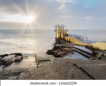 Blackrock public diving board, sun burst through cloudy sky over ocean, Galway city, county Galway, Ireland.
