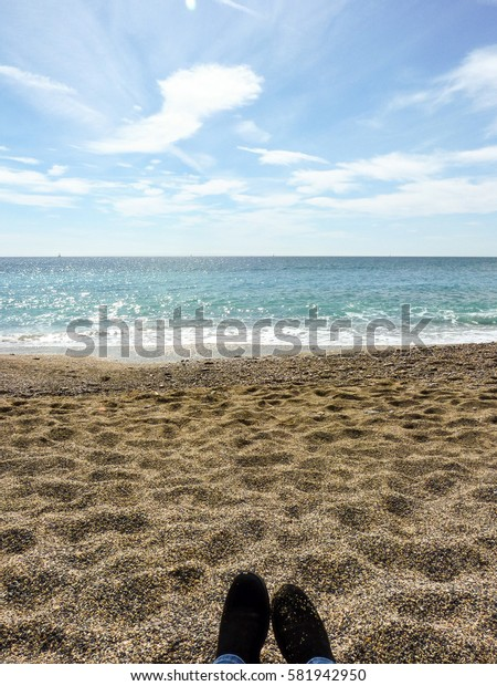 Blacks boots in front of the blue sea on white sandy beach background