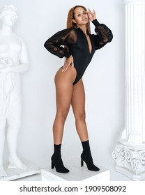 blackskin girl in black suit stands near white statues and columns photoshoot