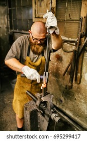 Blacksmith with beard working in his workshop