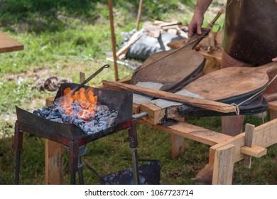 Blacksmith Blows Coals with Bellows in Outdoor Fair