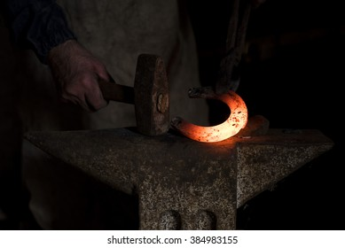 The blacksmith forging hot horseshoe with hammer on the anvil in smithy