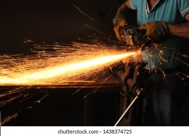 Blacksmith grindering a metal plate holding an angle grinder shot from above. The blacksmith work clothes in white blacksmith gloves grindering a metal plate