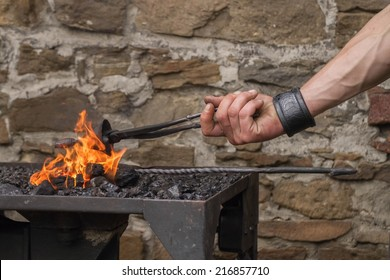 Blacksmith heating up a making small iron bell