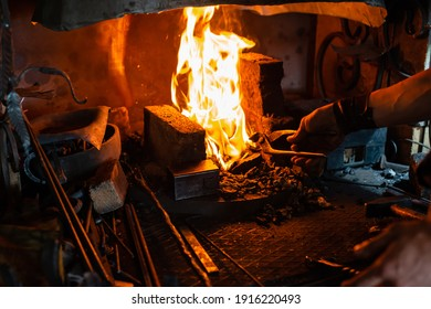 The blacksmith holds billet over hot coals in clay oven. blacksmith heating iron metal sword manufacturing marching forge, hands of a blacksmith hold piece of steel in fire of a red-hot forge