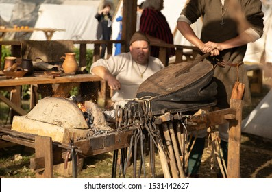A blacksmith inflates a flame with blacksmith furs. Blacksmith forge. Inflate furs. Reconstruction of old crafts. Middle Ages role-playing historical games. Master blacksmith. Metal tools. Clamp.