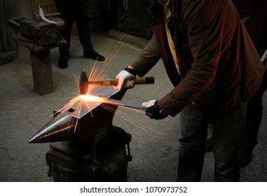 The blacksmith manually forging the molten metal on the anvil in smithy with spark fireworks. Spark. Dark background.