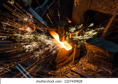 Blacksmith manually forging the molten metal on the anvil with spark fireworks