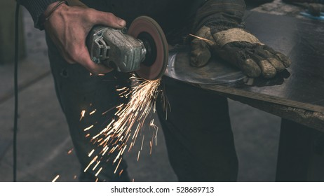 The blacksmith manually forging the molten metal on the anvil in smithy with spark fireworks - vintage look