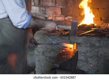 The blacksmith manually forging the molten metal on the anvil in smithy