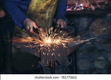 The blacksmith manually forging the molten metal on the anvil in smithy with spark fireworks, close up