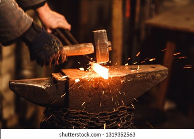 The blacksmith manually forging the red-hot metal on the anvil in smithy with spark fireworks