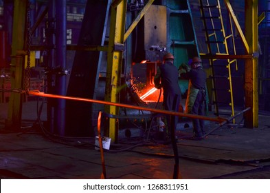 Blacksmith processes the iron product under a huge press, forging metal, stamping. Hot metal ingot being loaded in a hammer forge. Worker forges iron products. Metallurgical, forge plant