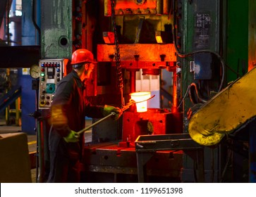 Blacksmith processes the red hot iron under a huge press. Metal forging, stamping under hammer forge at workshop of forge foctory. Blacksmithing, metallurgical, steelmaking, hot rolling mill