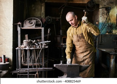 The blacksmith in the production process of metal products handmade in the workshop