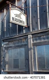 Blacksmith sign hanging on old barn