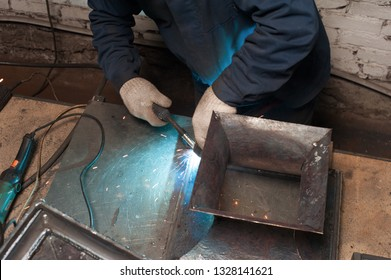 Blacksmith soldering metal plates to a metal stand with ornament. The blacksmith in white blacksmith gloves soldering metal stand in workshop