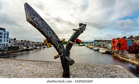Blacksmith structure with padlocks that sits on a bridge with the river Shannon and the village of Athlone in the background, wonderful sunny day in the county of Westmeath, Ireland