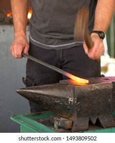 Blacksmith tools and actions forging iron objects.