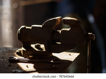 Blacksmith tools. Backlighted old vise in a forge shop