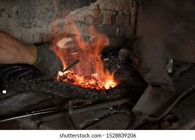 Blacksmith tools, traditional craft. Fire in the furnace. Smithy. Blacksmith's hand