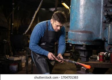 Blacksmith using blacksmith tongs for hot metal