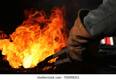 A  blacksmith at work with glowing irons. Hot iron forge, a blacksmith at work with red-hot iron.