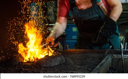 Blacksmith at work, hit with a hammer by a hot metal on the anvil.