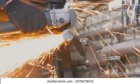 Blacksmith worker in forg making detail with circular saw