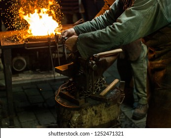 A blacksmith works with metal close to open fire. Christmas market in Prague, Czech Republic.