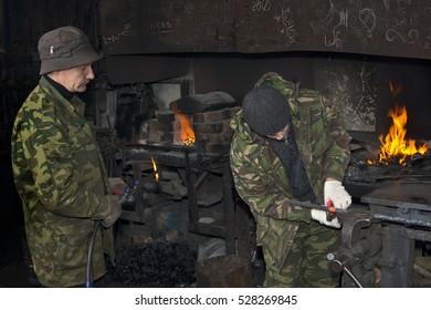 Blacksmith works in a small smithy