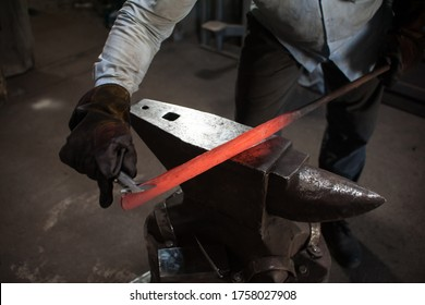 Blacksmithing. The blacksmith on the anvil measures the width of the split product. Photo of red metal close-up. The production of knives
