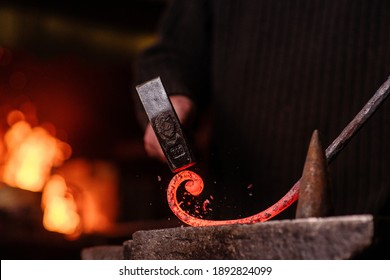 Blacksmithing. The blacksmith on the anvil measures the width of the split product and glowing sparks fly in all directions. Photo of red metal close-up.