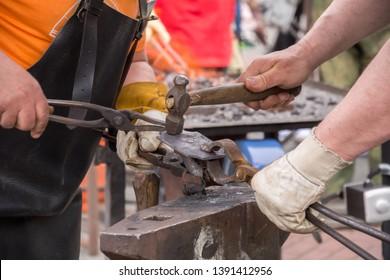 Blacksmiths make artistic smithing of hot metal on an anvil. Blacksmith hammer. Blacksmith tools